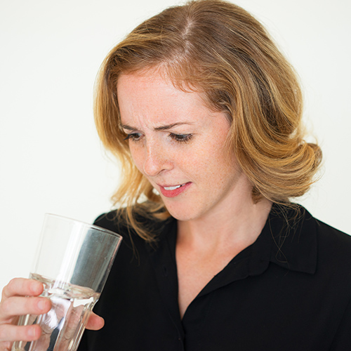 woman looking into water glass