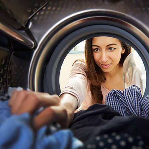 woman removing softened clothes from dryer
