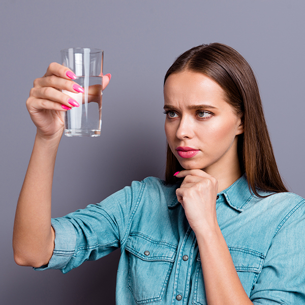 woman looking at glass of water