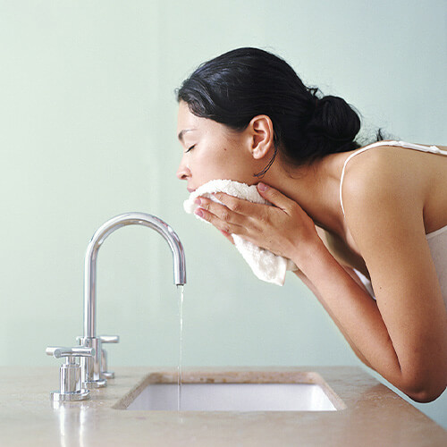 woman at sink washing face