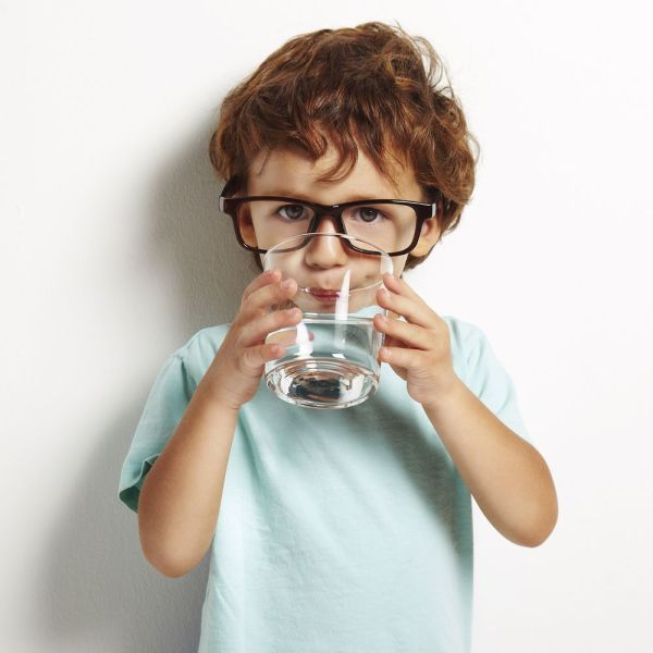 little boy drinking water from glass