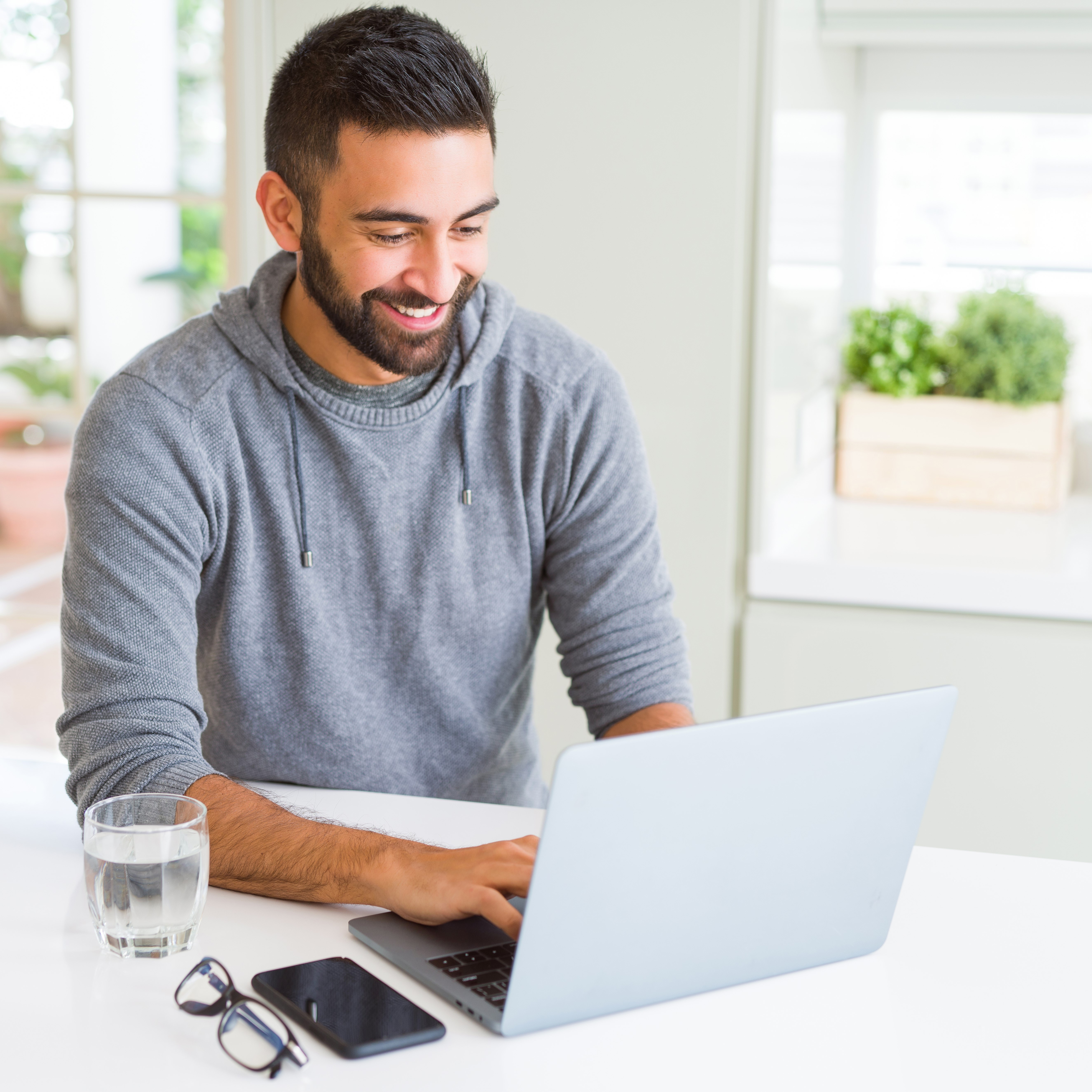 man working at computer and drinking water
