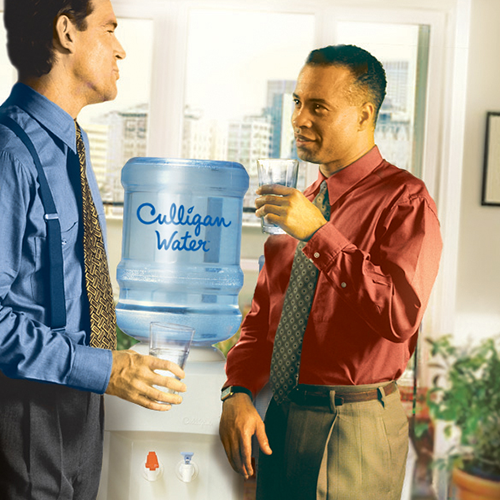 Office workers drinking from Culligan water dispenser