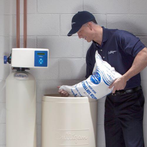 Culligan expert adding salt to water softener